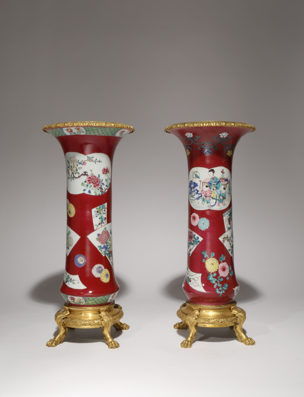 A NEAR PAIR OF CHINESE FAMILLE ROSE RUBY-GROUND ORMOLU-MOUNTED BEAKER VASES THE PORCELAIN 18TH