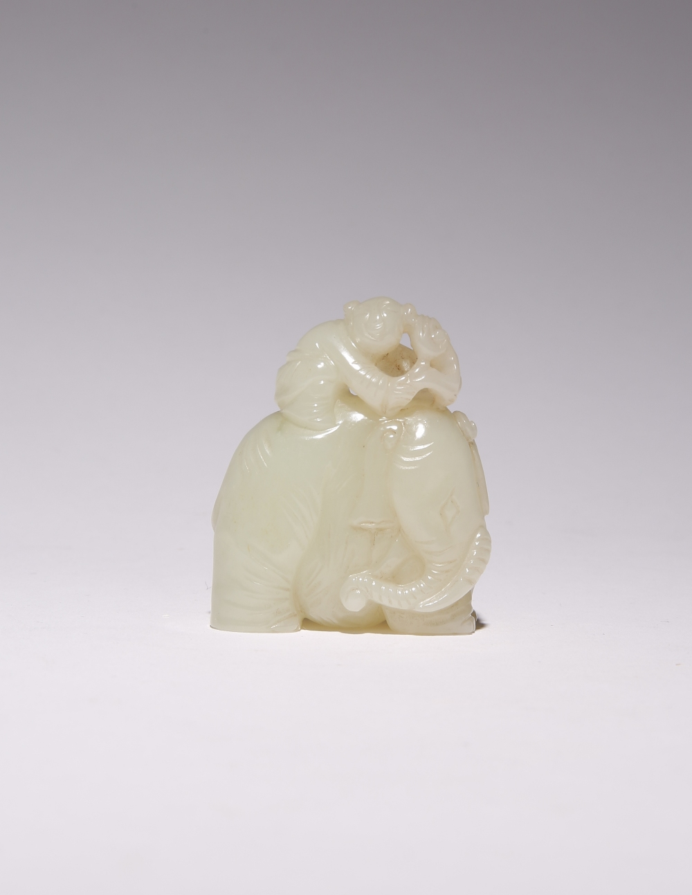 A CHINESE PALE CELADON JADE CARVING OF AN ELEPHANT QING DYNASTY OR LATER Formed as a small boy