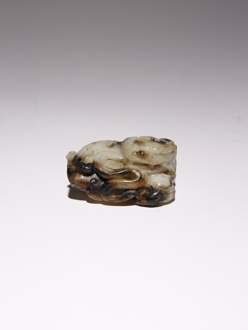 A CHINESE BLACK AND WHITE JADE CARVING OF A LION DOG QING DYNASTY The beast depicted lying down with