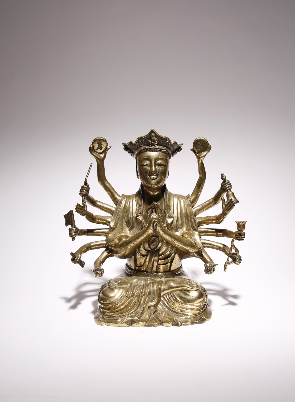 A CHINESE GILT-BRONZE FIGURE OF A FOURTEEN-ARMED BODHISATTVA QING DYNASTY The figure cast seated