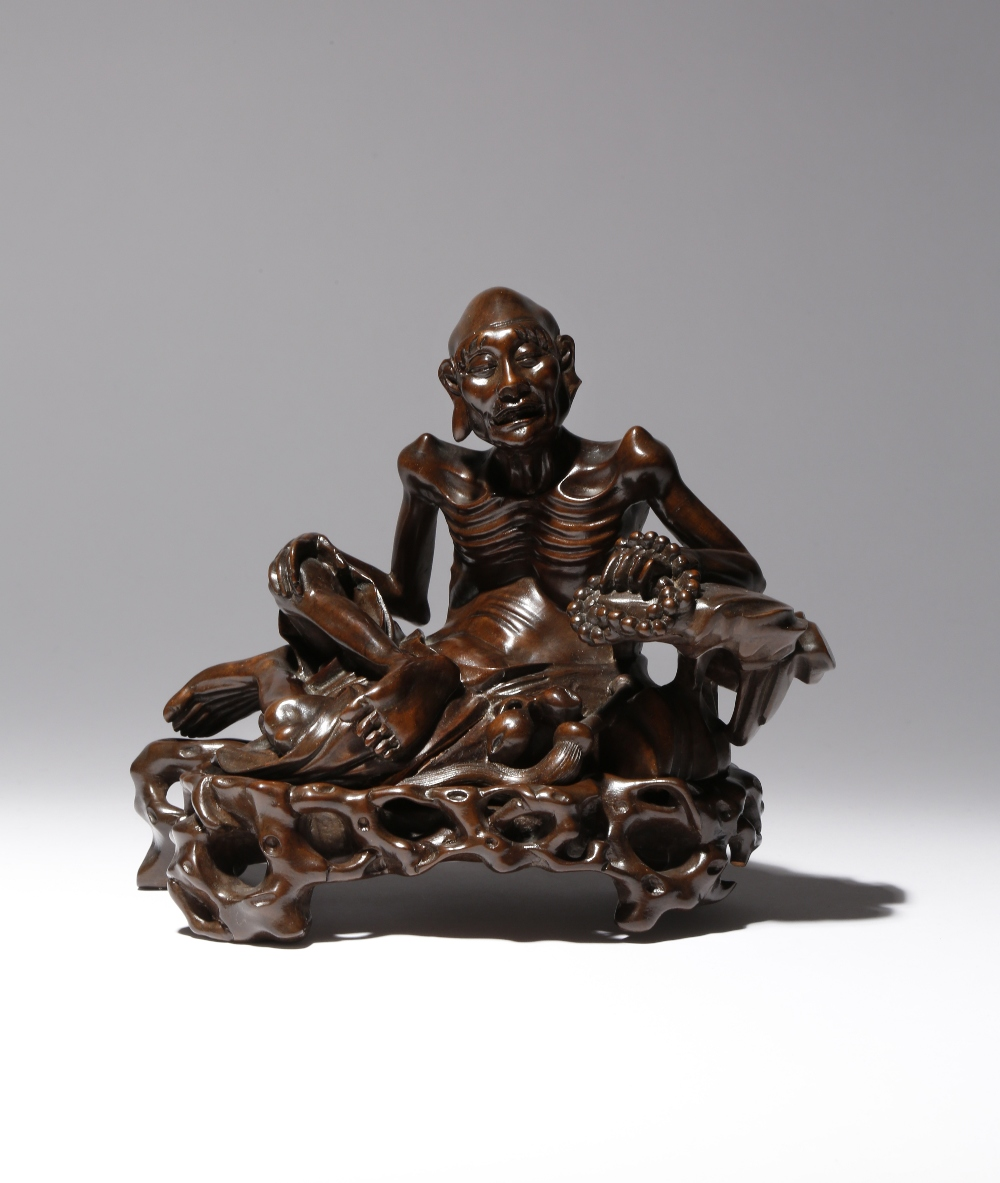 A CHINESE WOOD FIGURE OF AN ASCETIC LUOHAN LATE QING DYNASTY The emaciated figure seated resting his