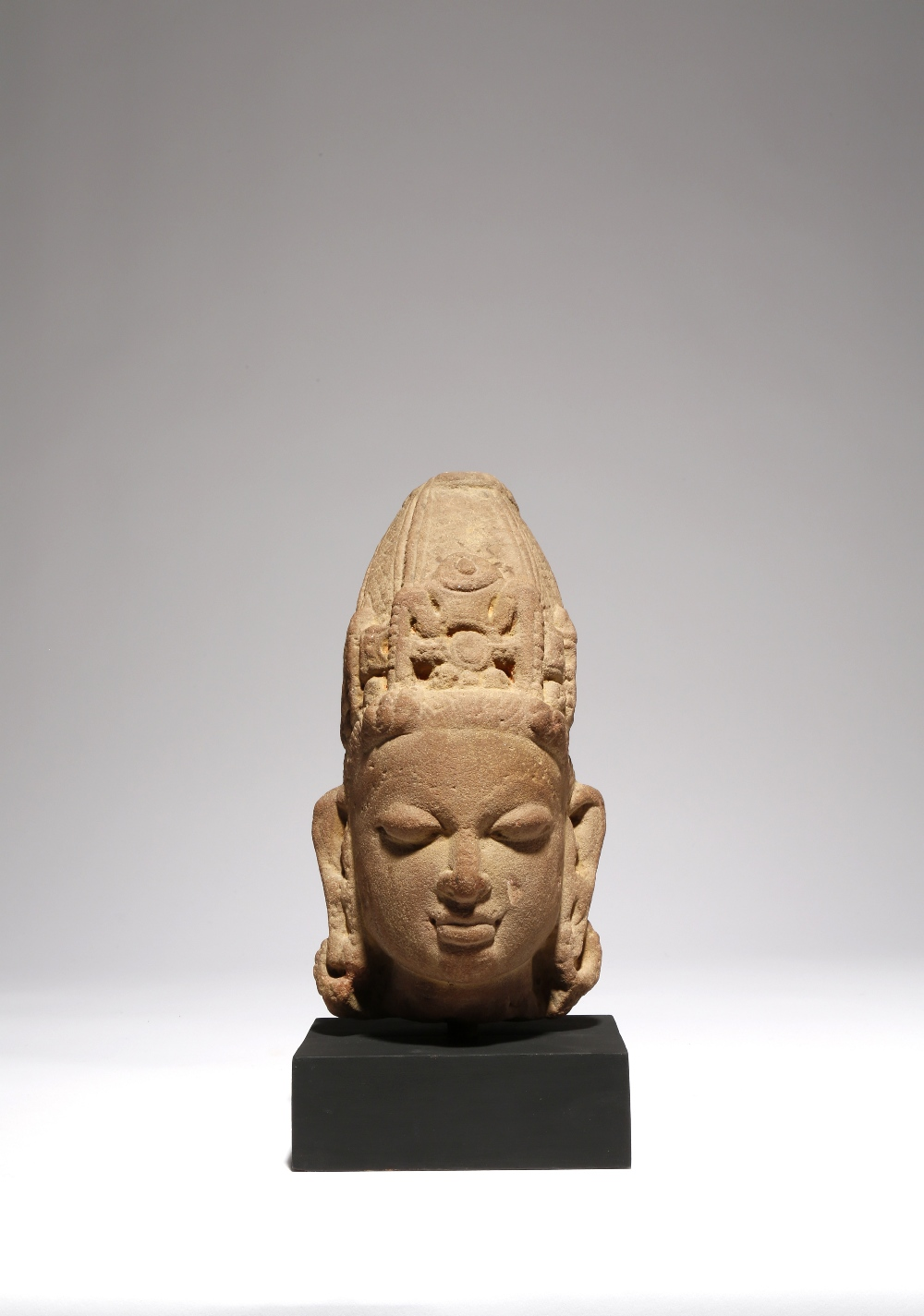 AN INDIAN RED SANDSTONE CARVING OF THE HEAD OF A DEITY C.11TH CENTURY Probably Rajasthan, his serene