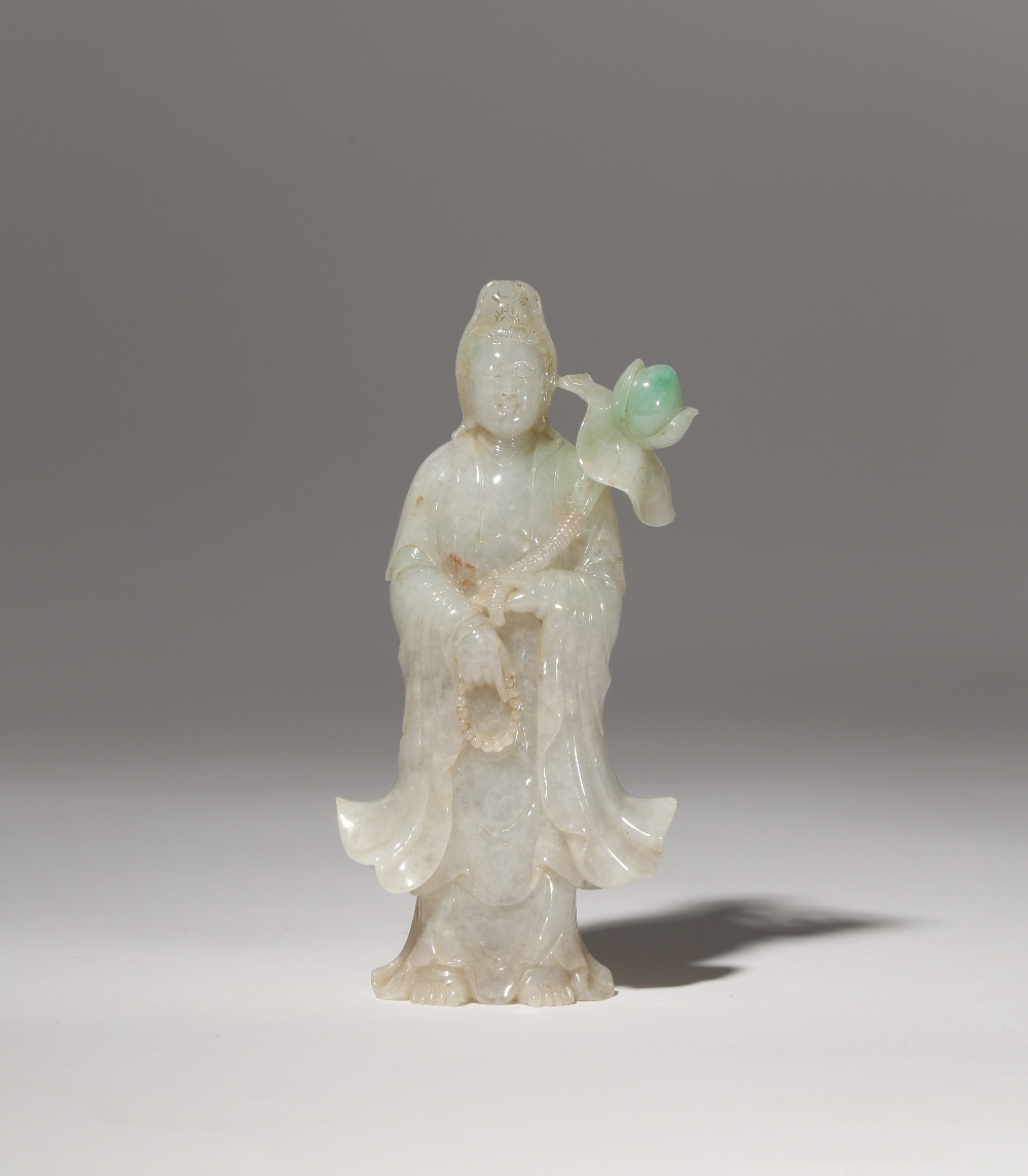 A CHINESE APPLE GREEN JADEITE FIGURE OF GUANYIN LATE QING DYNASTY The goddess stands wearing a