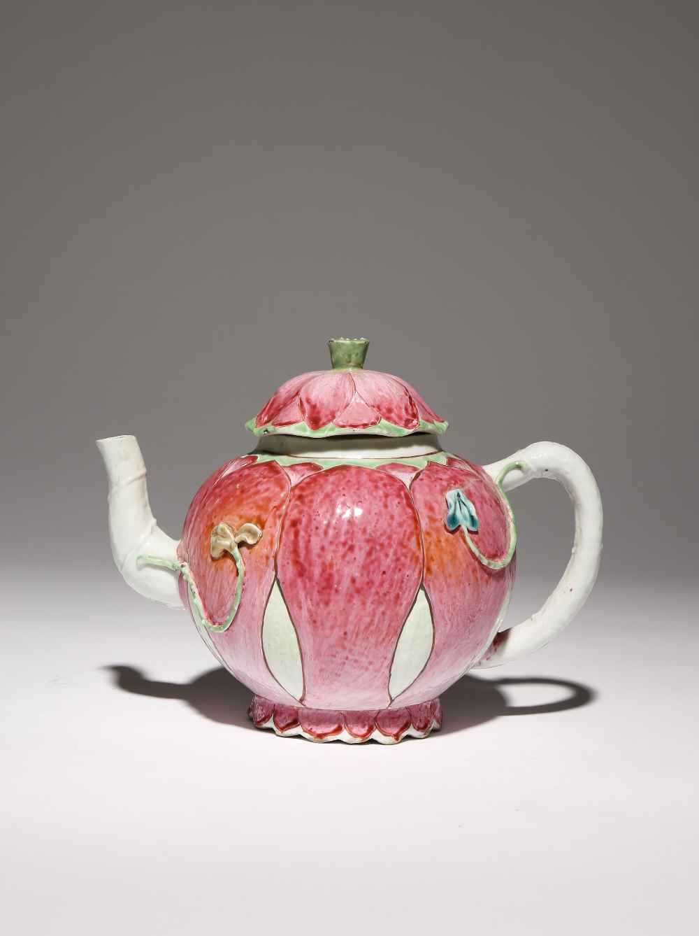 A CHINESE FAMILLE ROSE MOULDED 'LOTUS' TEAPOT AND COVER 18TH CENTURY The body brightly painted