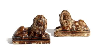 A PAIR OF STAFFORDSHIRE POTTERY LIONS LATE 18TH / EARLY 19TH CENTURY with a Whieldon-type glaze, the