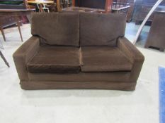 A vintage two seat club style sofa with brown upholstery, loose seat and back cushions, 146 cm long