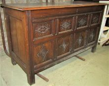An antique oak coffer with hinged lid, moulded panelled frame, the front elevation with lozenge