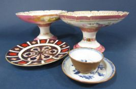 A matched pair of 19th century pink ground comports, one with reserved painted panels of chateaux,