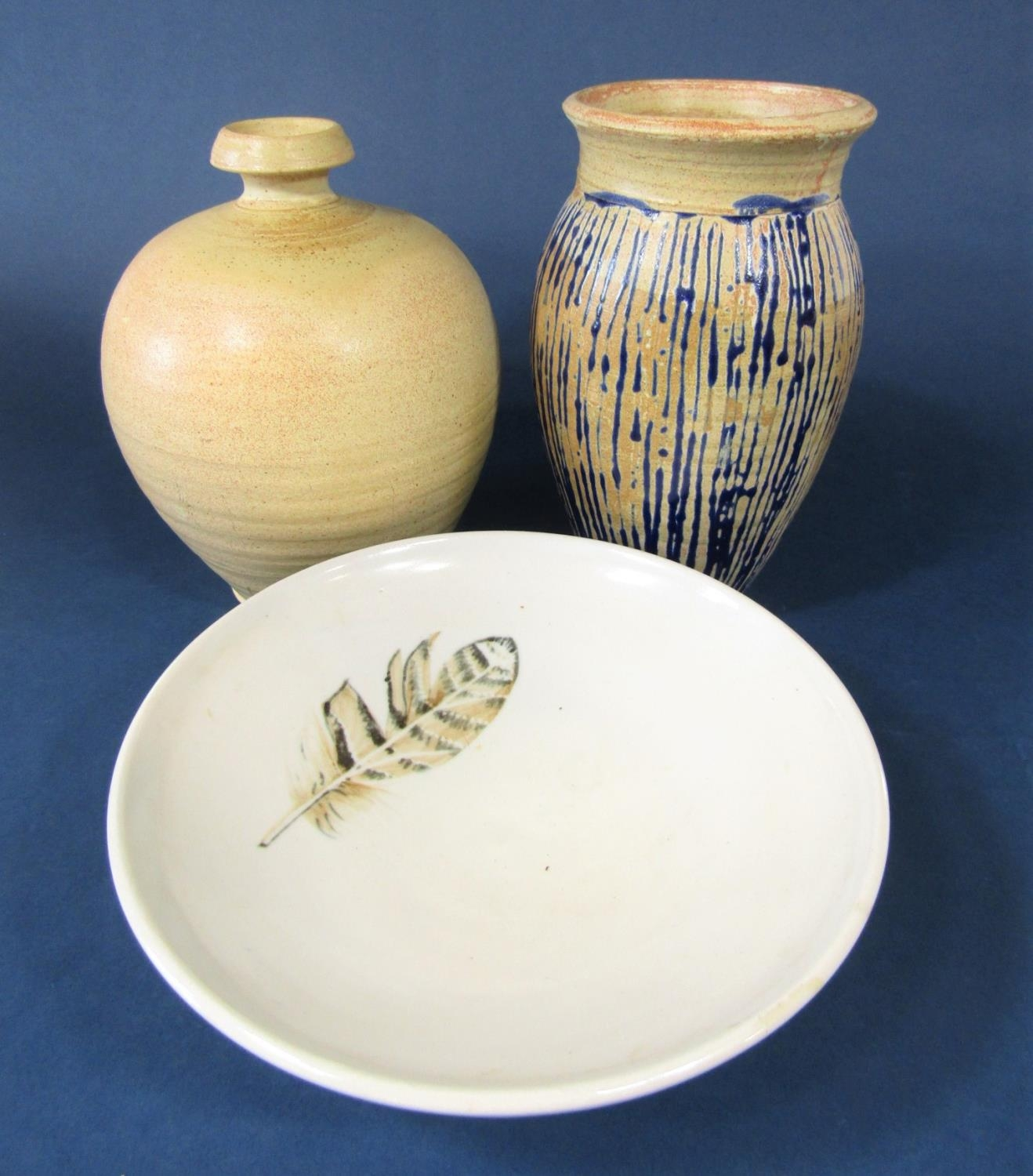 A studio pottery bowl of shallow form with painted feather detail and moulded mark to base
