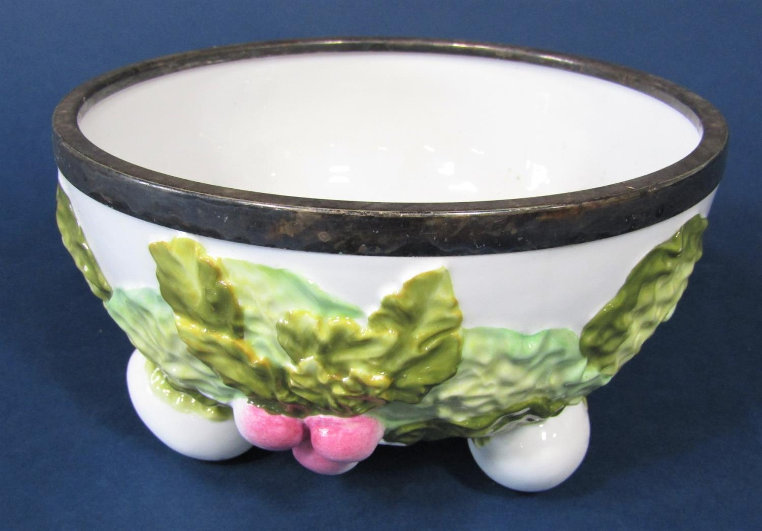 A 19th century majolica type bowl modelled and lettuce and radishes, raised on three egg shaped