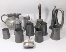 A 19th century pewter jug four pint capacity, a Victorian brass hand bell with turned wood handle,