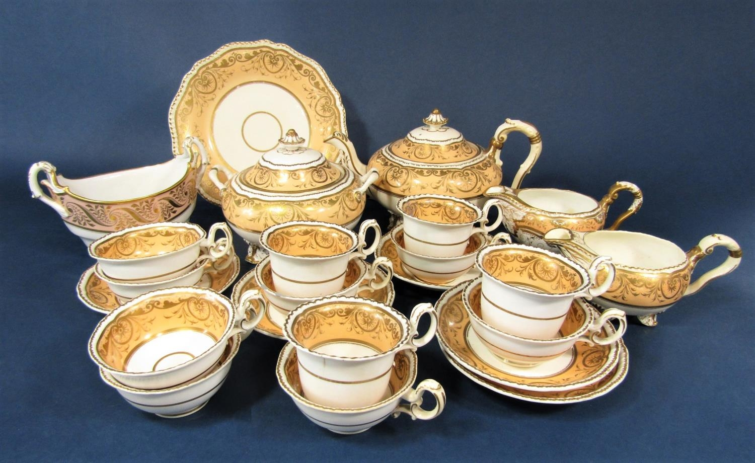 A collection of mid 19th century teawares with gilt scrolling decoration on a peach ground