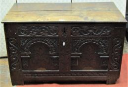 A 17th century oak coffer, the front elevation enclosing two arcaded panels with floral marquetry