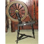 A traditional foot pedal operated spinning wheel, dark stained, principally in oak with turned