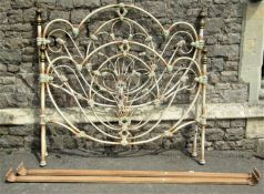 A Victorian style tubular steel framed double bedstead with arched and scrolled rails, with