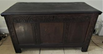 An 18th century oak panelled coffer with repeating geometric detail, 130cm wide