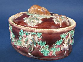 A 19th century majolica game dish and cover with relief moulded game bird and fruiting vine detail