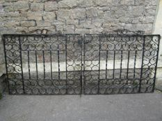 A pair of heavy gauge ironwork driveway entrance gates with S scroll detail, 240 span x 104 cm high