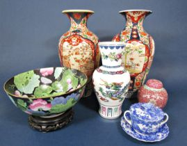 A pair of large oriental vases in the Imari manner with painted garden and bird detail, 37.5 cm tall