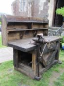 A vintage and rustic workshop bench of thick pine boarded construction, raised and shelved back over