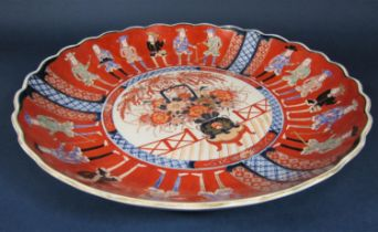 A large oriental charger in the 18th century imari style with flower vase detail to the centre