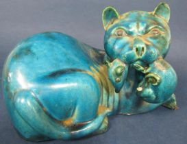 An unusual oriental turquoise glazed model of a fierce cat with a rat in its jaws (af), 28 cm long