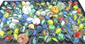 A collection of old looking marbles, spread over two canisters