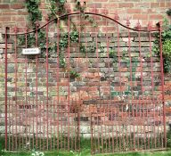 A pair of heavy gauge ironwork entrance gates of sloping arched form, with open vertical rails and