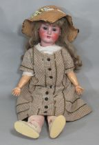 An early 20th century German bisque head doll by Schoenau & Hoffmeister, 1906, mould 15, with blue