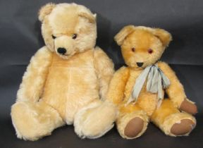 2 large teddy bears, both with jointed body, golden fur, glass eyes and stitched nose and mouth.