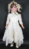 An early 20th century German bisque head doll by Schoenau & Hoffmeister, marked '915 12½' with brown