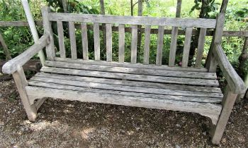 A weathered teak wood garden bench to commemorate the 1977 Silver Jubilee, 153cm wide