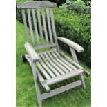 A weathered teak garden reclining chair, mounted on a single axle (lacks foot rest)