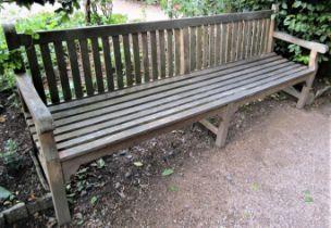 A weathered teak wood garden bench, 240cm wide