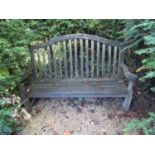 A weathered teak wood garden bench, with scrolled arms and slatted back, 100cm wide