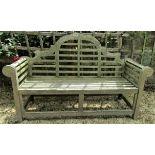 A weathered teak wood garden seat in the Lutyens manner, 165cm wide