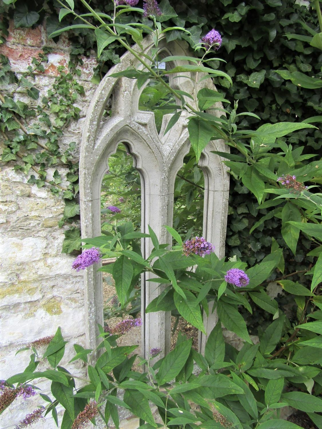 A Gothic style niche window with moulded detail incorporating mirror panels, (composite) 145cm