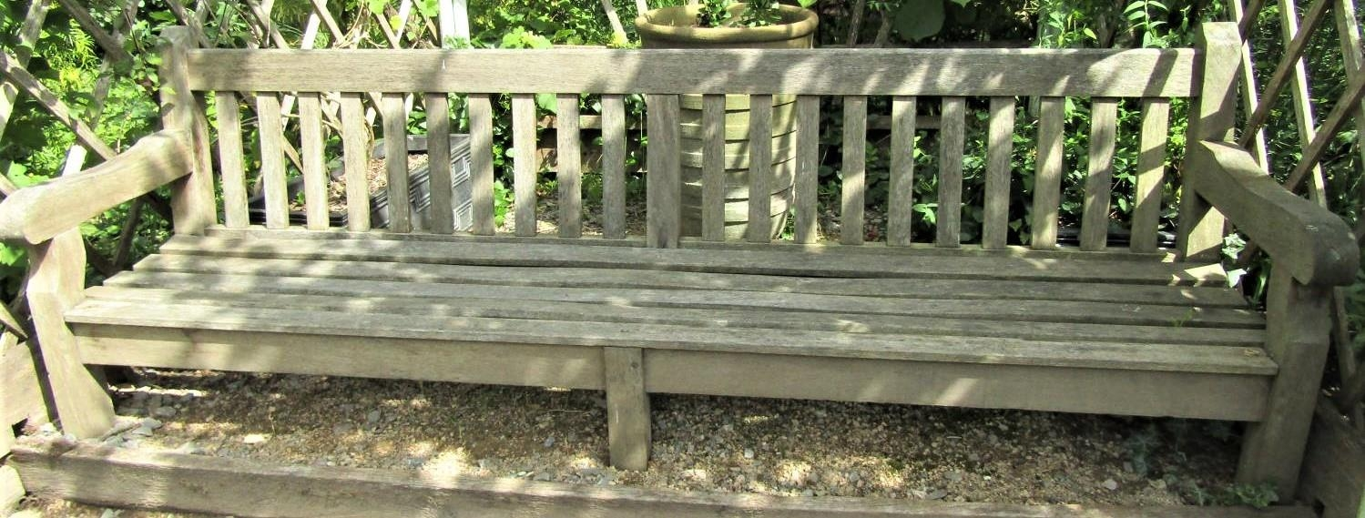 A weathered teak wood garden bench, 240cm wide, reduced in height