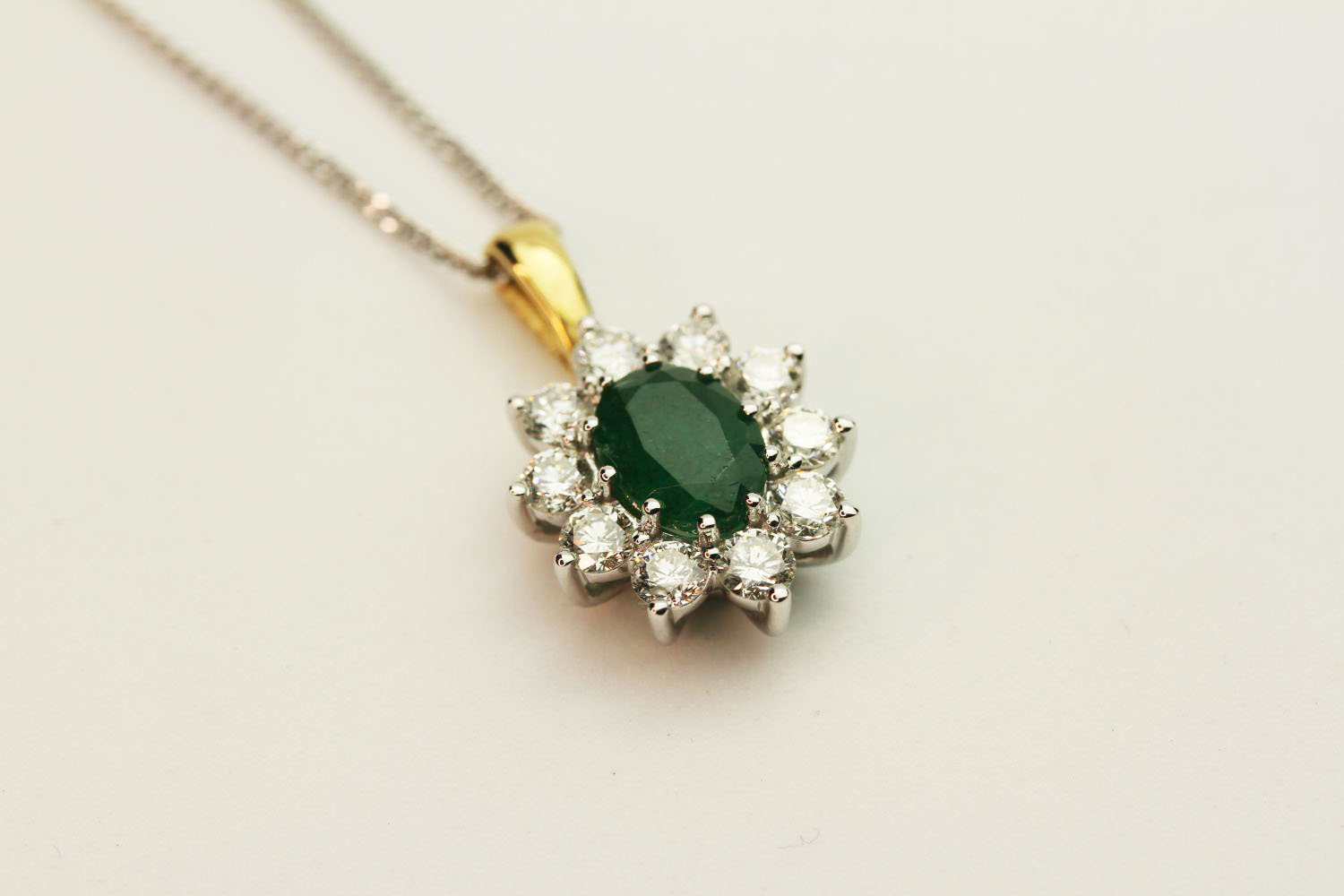 18ct white and yellow gold oval emerald and diamond cluster pendant on a silver chain, boxed.