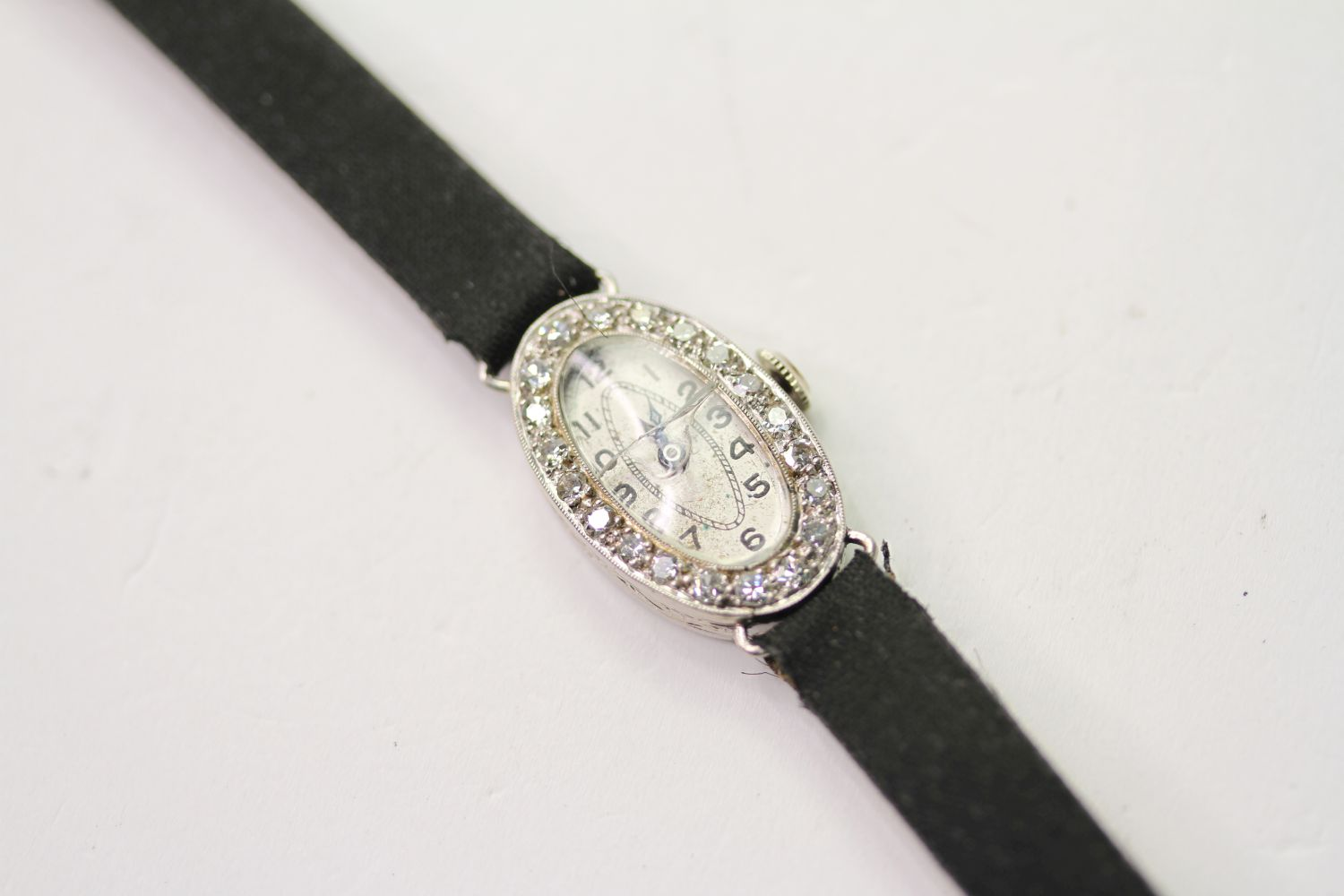 PLATINUM & DIAMOND COCKTAIL WRISTWATCH, oval silver dial with arabic numbers, 14mm case, diamond set