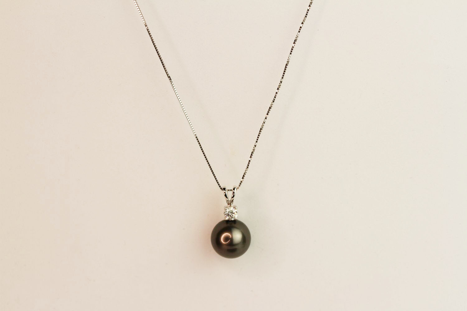 9ct white gold Tahitian black pearl pendant with diamond bale on a 10ct white gold chain, boxed.