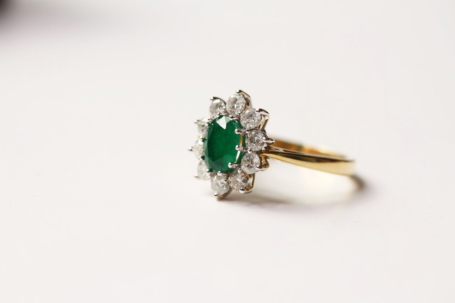 Emerald & Diamond Ring, set with an oval cut emerald, surrounded by 10 round brilliant cut diamonds,