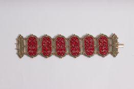Pulsera en plata dorada, esmalte rojo y piedras talla redonda, verdes y negras.