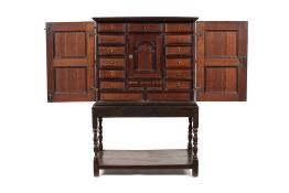 A 17th century Dutch oak and purpleheart cabinet on later stand