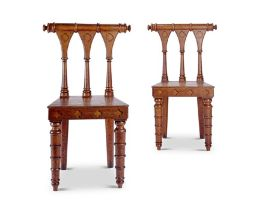 A pair of unusual George IV gothic carved oak hall chairs