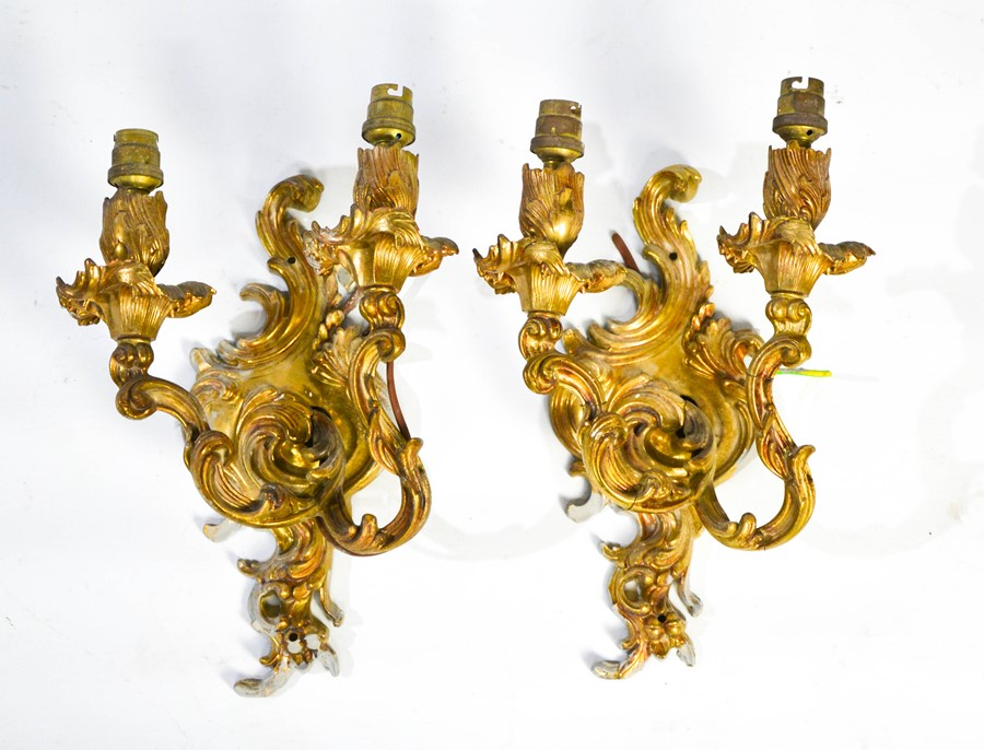 A pair of brass Rococo style wall lights both with two scrolling branches, 31cm high.