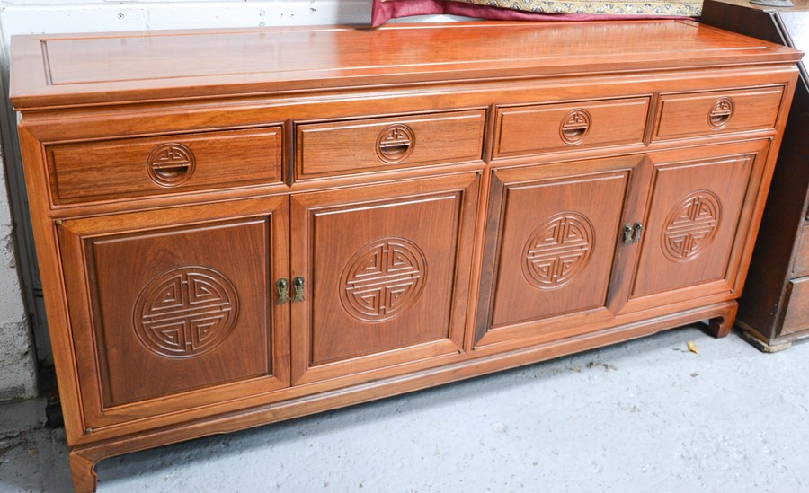 A 20th century Chinese rosewood sideboard with four drawers above corresponding cupboard doors