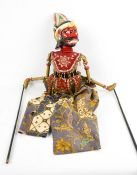 An Indonesian hand painted wooden puppet, with embroidered clothing and silk screen fabric.