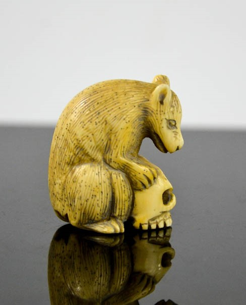 A Chinese ivory carved netsuke in the form of a wolf cub and skull, signed to the base, 4cm high. - Image 2 of 2