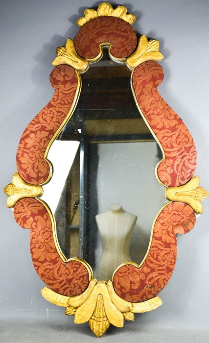 An antique gold painted and fabric lined scroll work wall mirror, 105 by 66cm.
